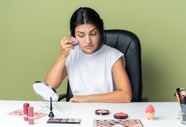 거울을 보고 있는 아름다운 여성은 스펀지로 톤 크림을 바르는 메이크업 도구를 가지고 테이블에 앉아 있다