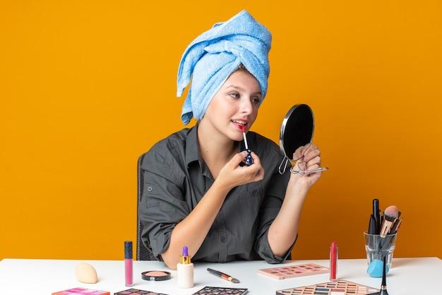 거울을 보고 있는 아름다운 여성은 립글로스를 바르는 수건에 머리를 감싼 화장 도구로 테이블에 앉아 있다