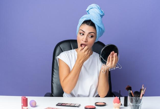 鏡を見て美しい女性が口紅を塗るタオルで髪を包んだ化粧ツールでテーブルに座っています