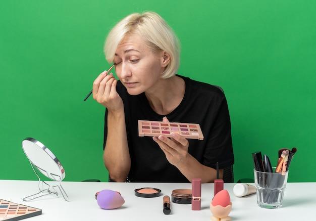 Глядя в зеркало, молодая красивая девушка сидит за столом с инструментами для макияжа, применяя тени для век с кистью для макияжа, изолированной на зеленой стене