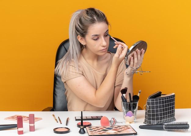 거울을보고 아름 다운 소녀 메이크업 도구 오렌지 벽에 고립 된 메이크업 브러시로 아이 섀도를 적용 테이블에 앉아
