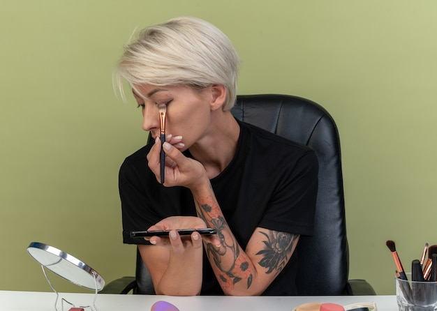 鏡を見て若い美しい少女は、オリーブグリーンの壁に分離された化粧ブラシでアイシャドウを適用する化粧ツールでテーブルに座っています