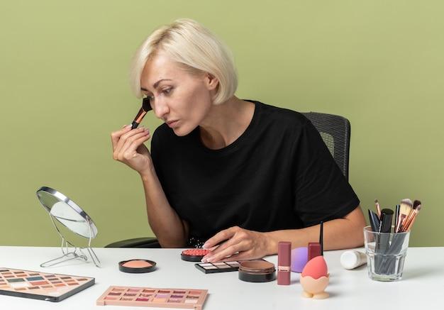 Глядя в зеркало, молодая красивая девушка сидит за столом с инструментами для макияжа и наносит румяна на оливково-зеленую стену