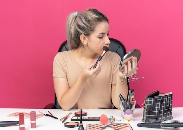 Глядя в зеркало, молодая красивая девушка сидит за столом с инструментами для макияжа и наносит румяна на розовую стену