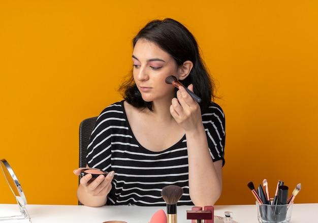 Глядя в зеркало, молодая красивая девушка сидит за столом с инструментами для макияжа и наносит румяна кистью, изолированной на оранжевой стене
