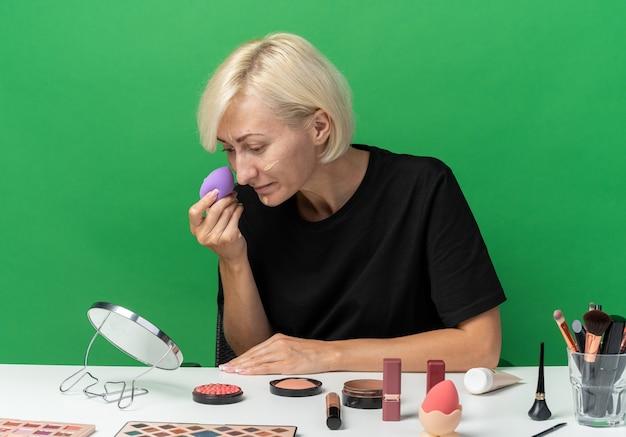 鏡を見て若い美しい少女は、緑の壁に分離されたスポンジでトーンアップクリームを適用する化粧ツールでテーブルに座っています