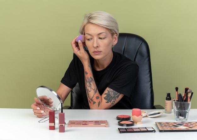鏡を見て若い美しい少女は、オリーブグリーンの壁に分離されたスポンジでトーンアップクリームを適用する化粧ツールでテーブルに座っています