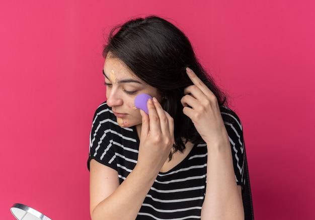 Глядя в зеркало, молодая красивая девушка сидит за столом с инструментами для макияжа и наносит тональный крем с губкой, изолированной на розовой стене