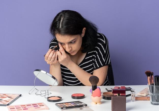 거울을보고 젊은 아름 다운 소녀 메이크업 도구와 테이블에 앉아 아이 라이너 파란색 벽에 고립 된 화살표를 그립니다