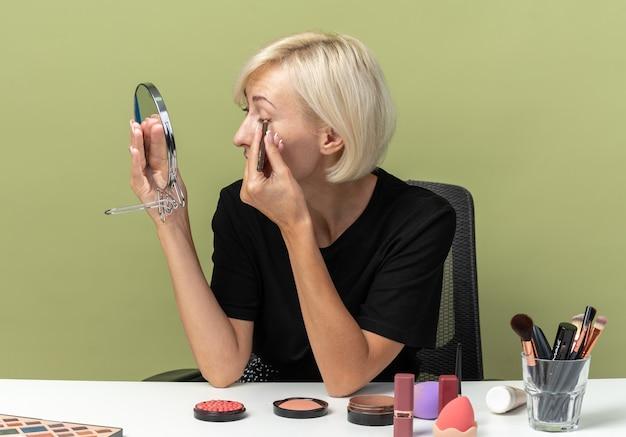 거울을보고 아름 다운 소녀 메이크업 도구와 테이블에 앉아 올리브 녹색 벽에 고립 된 아이 라이너와 화살표를 그립니다