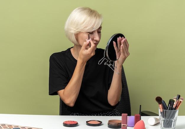 Глядя в зеркало, молодая красивая девушка сидит за столом с инструментами для макияжа, нарисуйте стрелку с подводкой для глаз, изолированную на оливково-зеленой стене