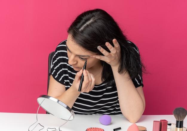 거울을보고 아름 다운 소녀 메이크업 도구와 테이블에 앉아 아이 라이너 핑크 벽에 고립 된 화살표를 그립니다