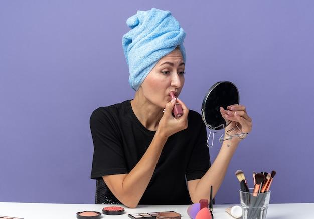 거울을보고 아름 다운 소녀 메이크업 도구 파란색 벽에 고립 된 립스틱을 적용 수건에 머리를 닦아 테이블에 앉아