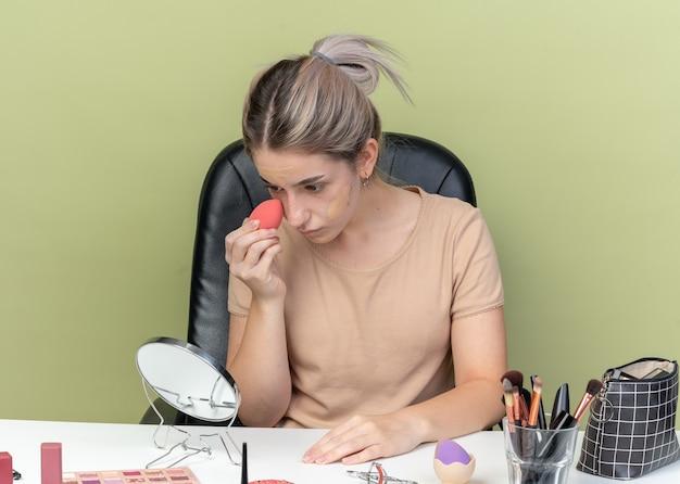 オリーブグリーンの壁に分離されたスポンジでトーンアップクリームを拭く化粧ツールで机に座っている鏡の若い美しい少女を見て