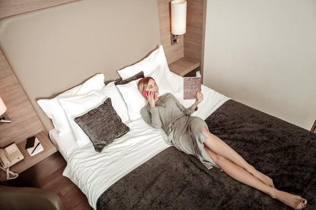 ノートブックを見てください。ノートブックを見ながらホテルのベッドに横たわっているスリムでスタイリッシュな実業家