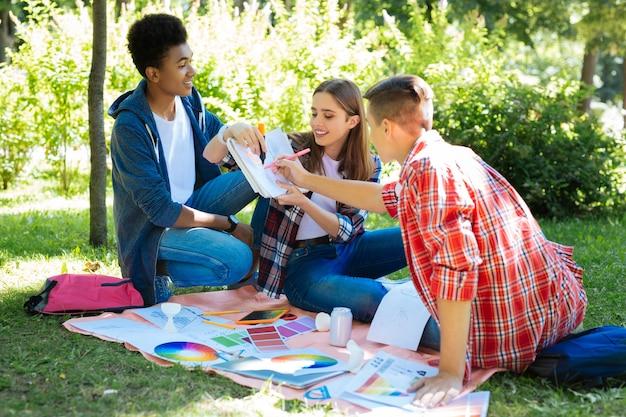 메모를보고 있습니다. 자연 속에 앉아 노트를 보면서 활동적인 느낌을주는 세 명의 창의적인 학생