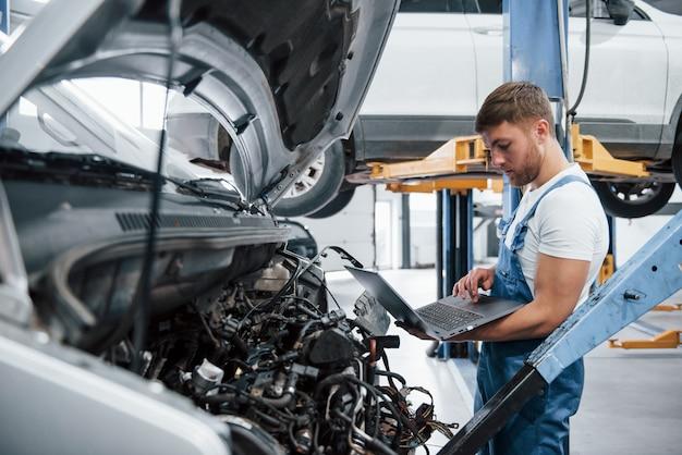 アイテムの価格を見てください。自動車のサロンで働く青い制服を着た従業員