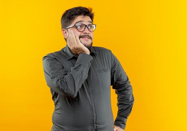 Молодой предприниматель в очках, положив руку под подбородок, изолирован на желтом фоне