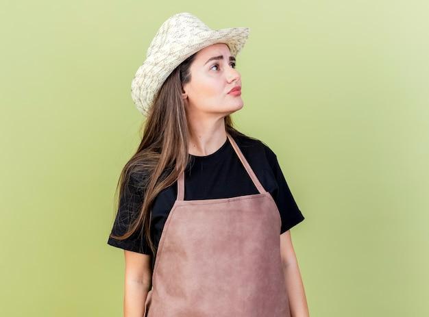 オリーブグリーンの背景で隔離の園芸帽子を身に着けている制服を着た美しい庭師の女の子の側を見て