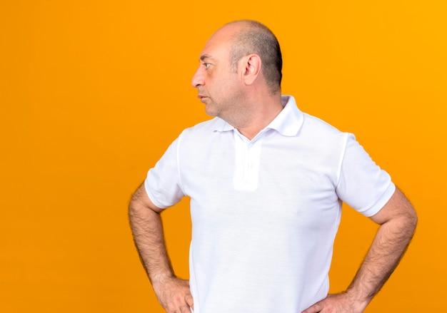 黄色の背景に分離された腰に手を置くカジュアルな成熟した男性の側を見て
