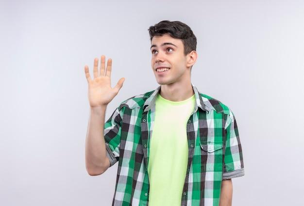 孤立した白い壁に挨拶を与える緑のシャツを着ている白人の若い男を見て