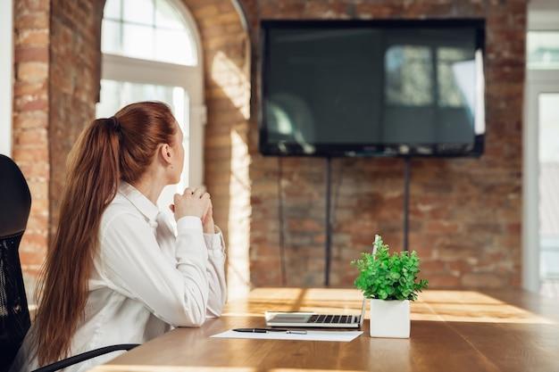 측면을보고 있습니다. 사무실에서 근무하는 비즈니스 복장에 백인 젊은 여자. 젊은 사업가, 스마트 폰, 노트북, 태블릿으로 작업을하는 관리자는 온라인 회의가 있습니다. 금융, 직업의 개념.