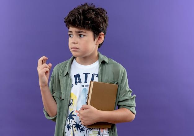 本を持っている小さな男子生徒と紫色の壁に隔離された交差する指に関係する側を見て