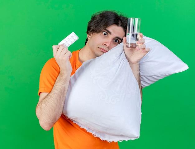 측면 우려 젊은 아픈 사람이 베개를 안아보고 녹색 배경에 고립 된 약으로 물 잔을 들고