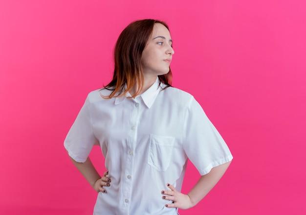 ピンクの背景に分離された腰に手を置く自信を持って若い赤毛の女の子を見て