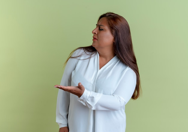 Глядя в сторону смущенная случайная кавказская женщина средних лет указывает рукой сбоку