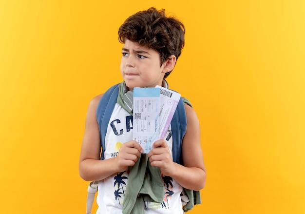 측면에서 찾고 다시 가방과 노란색 배경에 고립 된 티켓을 들고 헤드폰을 착용하는 작은 학교 소년 혼란