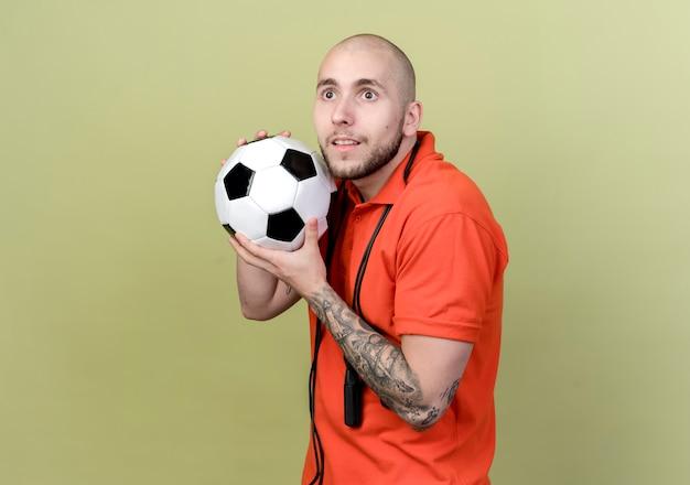 オリーブグリーンの壁に分離された肩に縄跳びで顔の周りにボールを保持している側面に感銘を受けた若いスポーティな男を見て