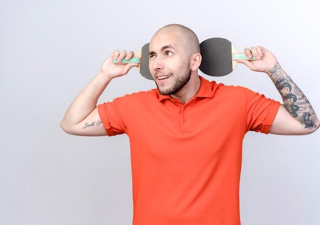 Глядя на сторону впечатлен молодой спортивный мужчина держит ракетку для пинг-понга за головой