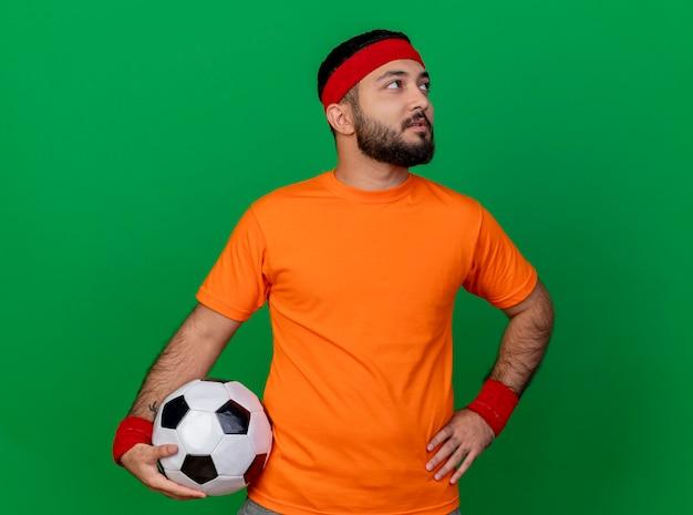 Глядя на сторону впечатленного молодого спортивного человека с повязкой на голову и браслетом, положившего мяч на бедро, изолированного на зеленом фоне