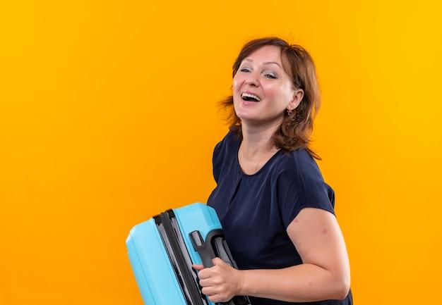 Глядя на сторону радостной путешественницы средних лет, держащей чемодан на изолированной желтой стене