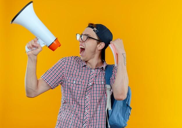 Глядя в сторону, радостный молодой студент-мальчик в задней сумке, очках и кепке говорит в громкоговоритель и показывает жест