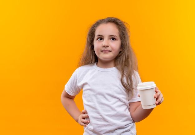 커피의 경찰을 들고 흰색 티셔츠를 입고 측면 작은 학교 소녀를보고 격리 된 오렌지 벽에 엉덩이에 그녀의 손을 넣어
