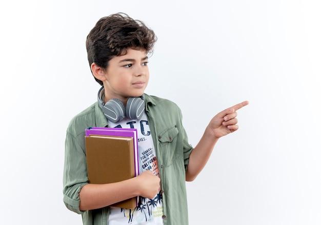 本を保持しているヘッドフォンを身に着けている側の小さな男子生徒を見て、コピースペースで白い背景で隔離の側のポイント