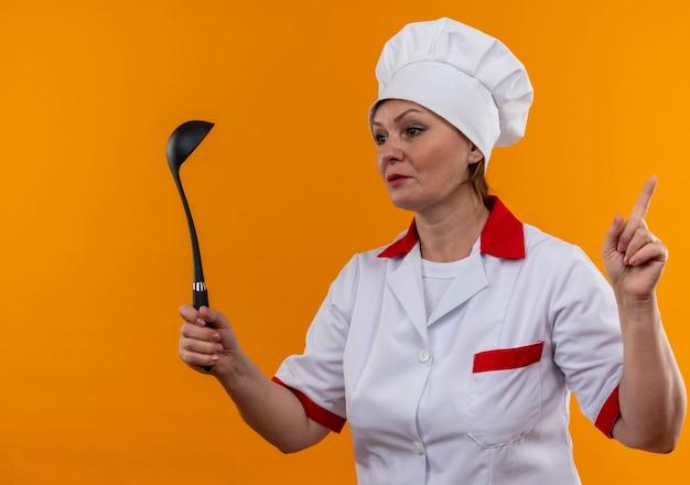 Глядя на сторону повара средних лет в униформе шеф-повара, держащего ковш, указывает пальцем вверх на изолированную желтую стену с копией пространства