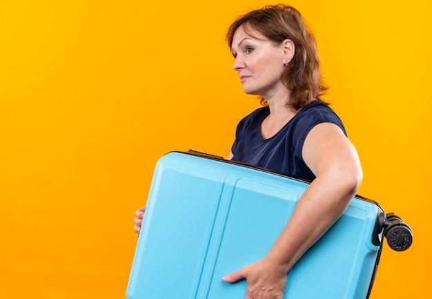 孤立した黄色の背景にスーツケースを保持している中年旅行者の女性の側を見て