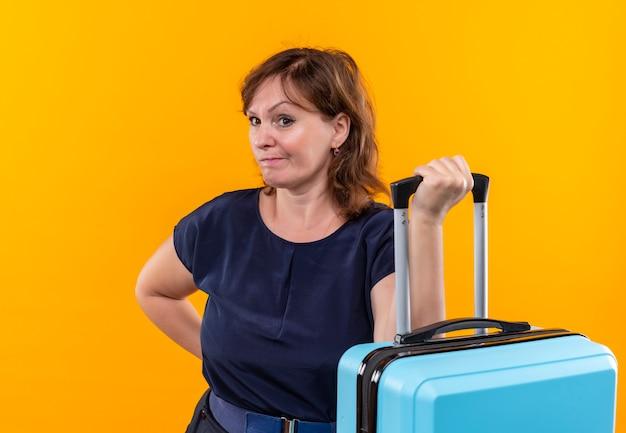 Глядя на женщину-путешественницу средних лет, держащую чемодан на изолированной желтой стене