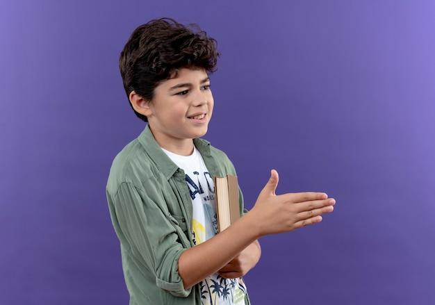 本を持ってバックバッグを身に着け、紫色の壁に隔離された手を左右に差し出して喜んでいる小さな男子生徒を横から見て