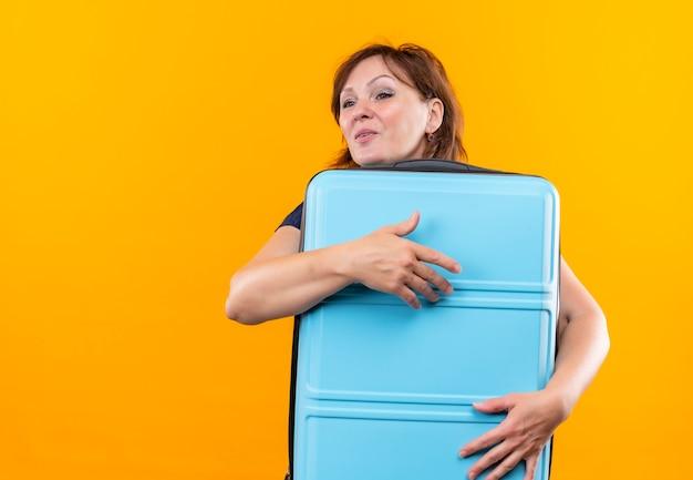 側面を見て満足している中年の旅行者の女性は、孤立した黄色の壁にスーツケースを抱きしめました