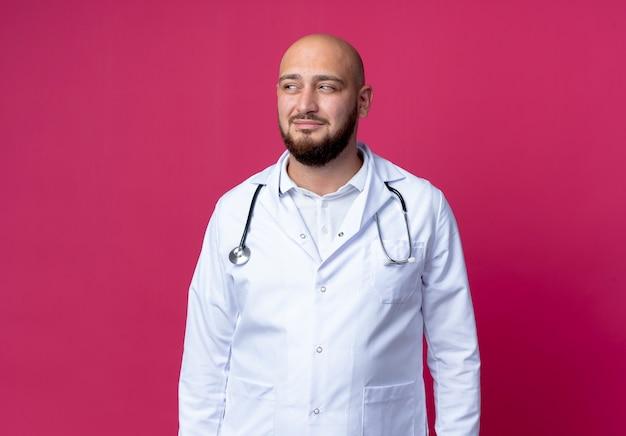 측면에서 찾고 의료 가운 및 복사 공간 분홍색 배경에 고립 된 청진기를 입고 젊은 대머리 남성 의사를 기쁘게