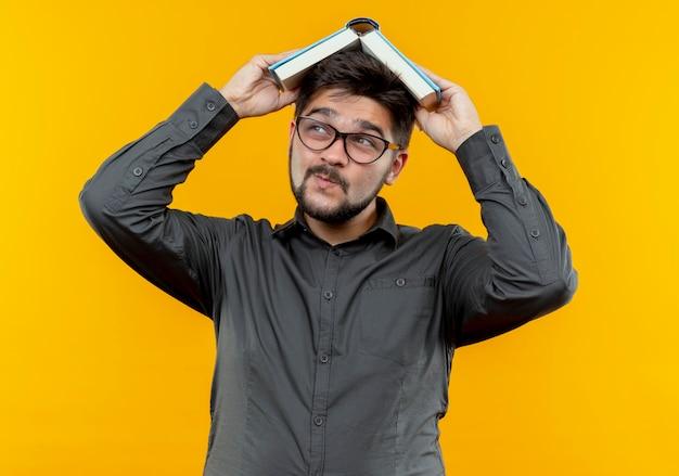 안경을 쓰고 측면 기쁘게 젊은 사업가 책으로 머리를 커버