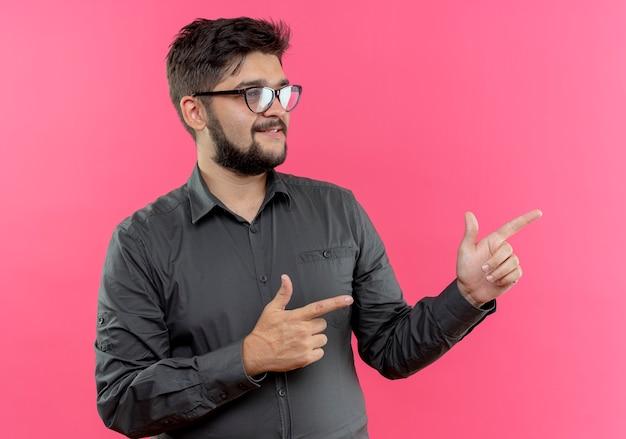 Глядя на сторону доволен молодой бизнесмен в очках указывает на сторону, изолированную на розовой стене с копией пространства