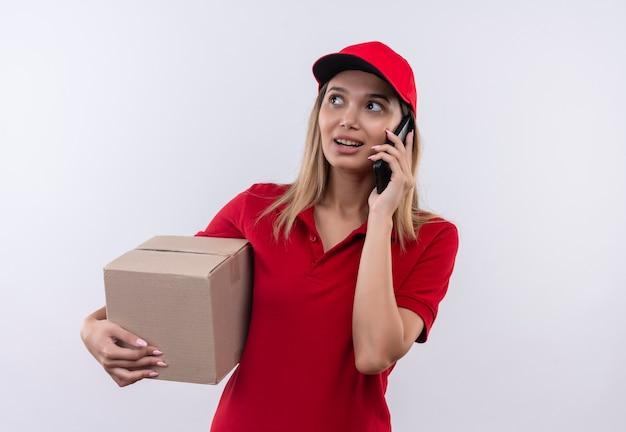 측면에서 찾고 빨간 유니폼과 모자를 들고 젊은 배달 소녀를 찾고 상자를 들고 흰색 벽에 고립 된 전화에 말한다