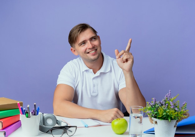 파란색 배경에 고립 된 측면에서 학교 도구 포인트와 책상에 앉아 측면을 기쁘게 젊은 잘 생긴 남자 학생을보고