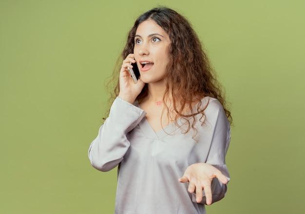 Глядя на сторону довольная молодая симпатичная офисная работница говорит по телефону, протянув руку, изолированную на оливково-зеленой стене