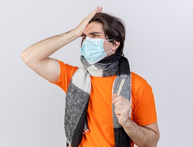 흰색 배경에 고립 된 이마에 손을 넣어 온도계를 들고 스카프와 의료 마스크를 착용 측면 후회 젊은 아픈 남자를보고
